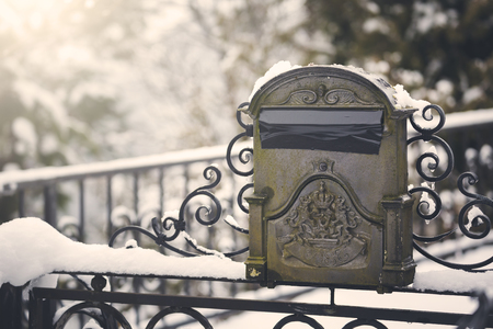 Old classic mailbox in front of home vintage style in winter, Austria