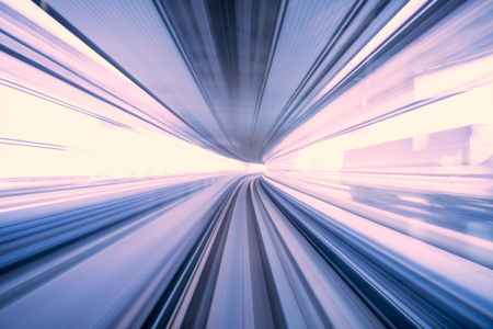 Motion blur of train moving inside tunnel with daylight in tokyo, Japan, purple color 免版税图像