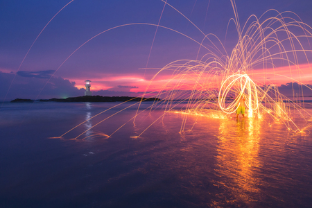 Fire steel wool with lighthouse and water reflection at sunset on beach in Thailand Reklamní fotografie
