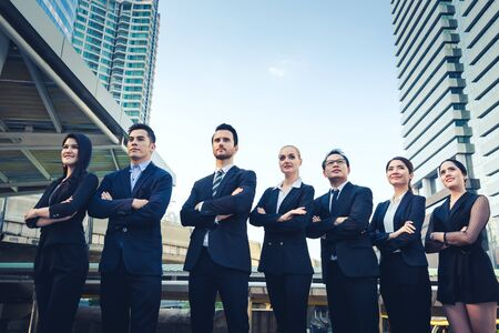Group of professional business team cross ones arm outdoor with office building background 写真素材
