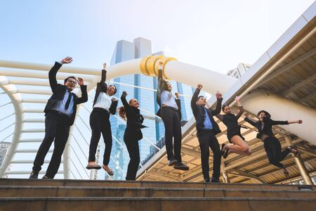 Group of successful professional business team are arm up and jumping for celebrating outdoor with office building background