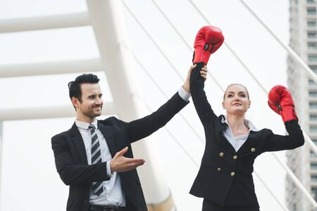 Business woman and man with red boxing gloves for win success and girl power concept against office building background Stok Fotoğraf - 132037832