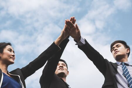 Business teamwork concept, Professional business man and woman team putting their hands together for Celebration unity on blue sky background, group of asian and caucasian nationality Standard-Bild