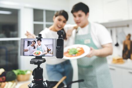 Vlogger and blogger freelance job concept, Young asian couple cooking together and recording live video for her vlog and social media with mobile phone camera and tripod