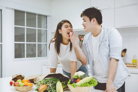 Romantic young asian couple cooking together in white modern kitchen with vegetable and fruit in paper bag Imagens
