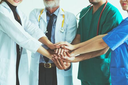Group of happy doctor surgeon and nurse putting their hands together for teamwork in meeting on white background, Healthcare and medical concept
