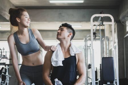 Fitness man and asian woman doing exercise and dumbbell weights in sport gym, healthy lifestyle concept