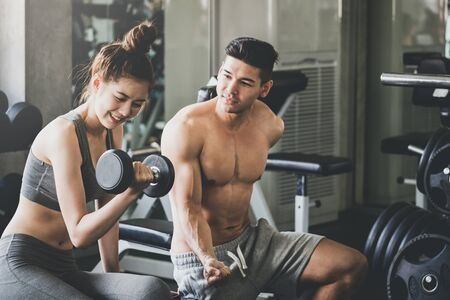 Fitness man and asian woman training exercise and lifting dumbbell weights together in sport gym, healthy lifestyle concept