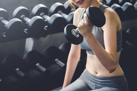 Fitness asian woman doing exercise and lifting dumbbell weights in sport gym, healthy lifestyle concept Imagens