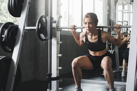 Fitness asian woman doing exercise and lifting barbell weights in sport gym, healthy lifestyle concept