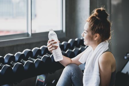 Fitness asian woman drinking water and resting after workout exercise in sport gym, healthy lifestyle concept