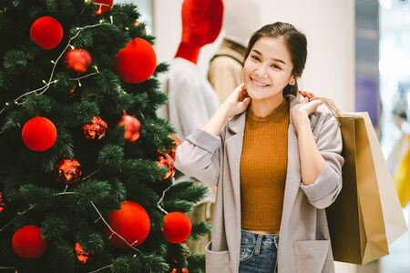Lifestyle shopping concept, Young happy smiling woman with paper bag against christmas tree decoration in shopping mall, vintage style