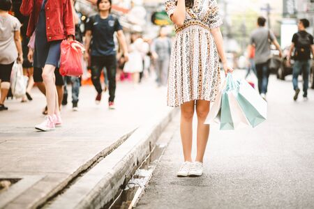 Lifestyle shopping concept, Young happy smiling woman with paper bag in shopping street at evening, vintage style