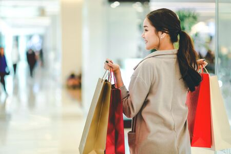 Lifestyle shopping concept, Young happy asian woman with paper bag and coat in shopping mall, vintage style 写真素材