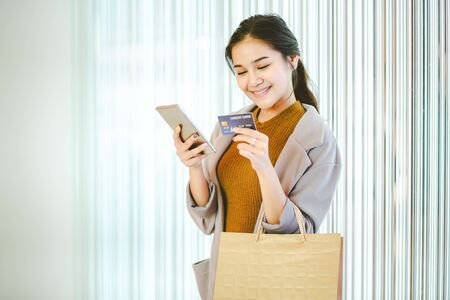 Lifestyle shopping concept, Young happy smiling woman with credit card, mobile phone and paper bag in shopping mall, vintage style