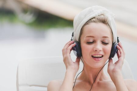Spa pool concept, Happy young woman holding headphone listening music with white Towel at swimming pool in spa resort