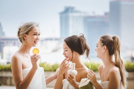 Spa pool concept, Group of happy young woman holding coconut water with half of orange and white Towel at swimming pool in resort Imagens