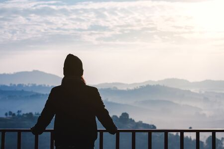 Young travel asian woman with sweater and Wool hat look at view of mountain and fog at morning in Khao Kho mountain, Phetchabun, Thailand, famous place in winter season Фото со стока