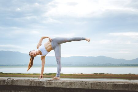 Asian woman with sport bra doing yoga fitness exercise for relax and healthy at lake in morning, Nature background, Concept outdoor sport and health 版權商用圖片