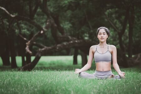 Fitness asian woman doing yoga exercise and relax with sportswear in green park at summer, healthy lifestyle concept