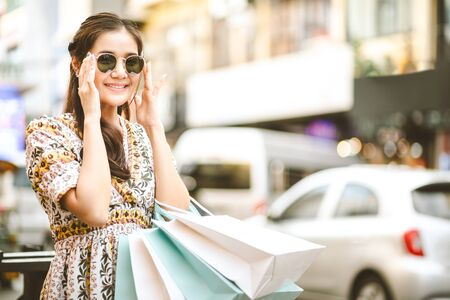 Lifestyle shopping concept, Young happy smiling woman with paper bag and sunglass in shopping street at evening, vintage style