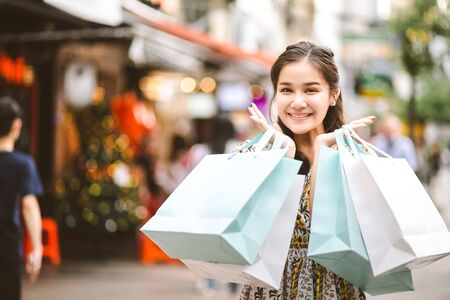 Lifestyle shopping concept, Young happy smiling woman with paper bag and dress in shopping street at evening, vintage style 写真素材