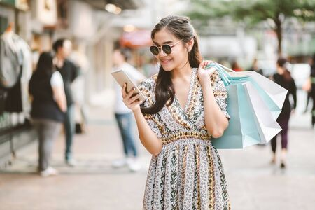 Lifestyle shopping concept, Young happy smiling woman with mobile phone and paper bag in shopping mall, vintage style
