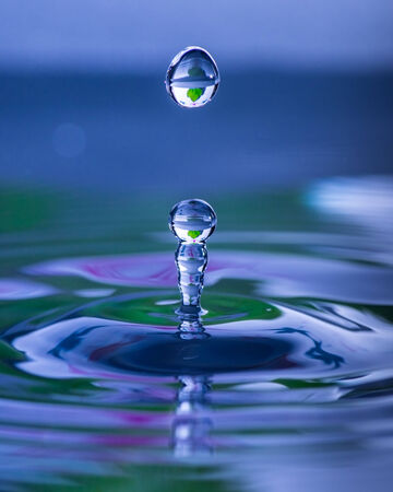 Splash and droplet rising from waters surface after impact of water drop Stock Photo