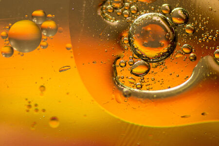 Oil and water mixing and forming bubbles and droplets