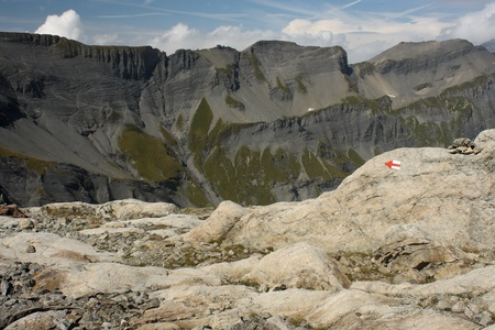 steep cliffs sign: red arrow painted on rock in Rhone-Alpes