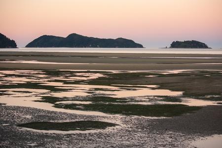 tasman: water pools at beach in Sandy Bay at sunset Stock Photo