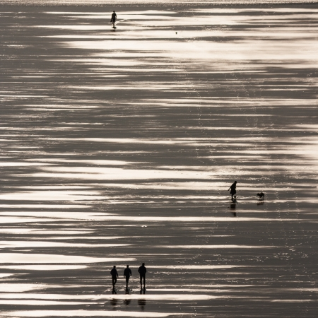 silhouettes of people strolling on beach photo