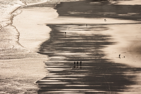 silhouettes of people strolling on Piha beach at low tide photo