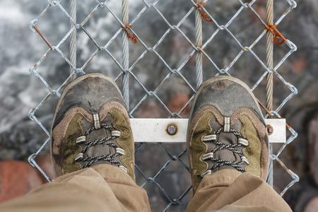 walking boots: detail of walking boots on suspension bridge