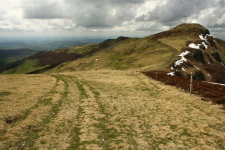 cantal: rolling hills with grass in Monts du Cantal Stock Photo