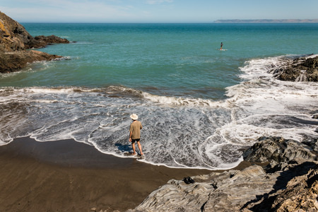 man strolling on volcanic beach in Whites Bay Stock Photo