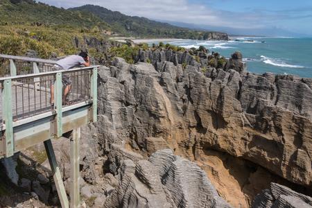 man taking pictures of Pancake rocks at Punakaiki photo