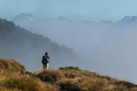 photographer taking pictures of misty mountains photo