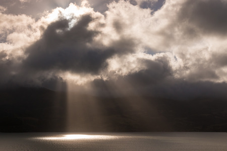 rays of light breaking through stormy clouds Stock Photo