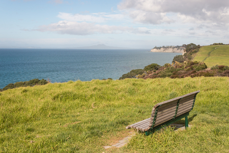 long bay: empty bench on green meadow above Long Bay Stock Photo