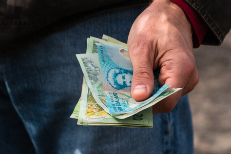 detail of hand holding New Zealand dollars