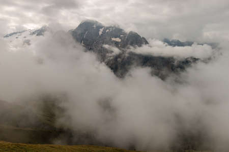 obscured: mountain range in Dolomites obscured by clouds Stock Photo