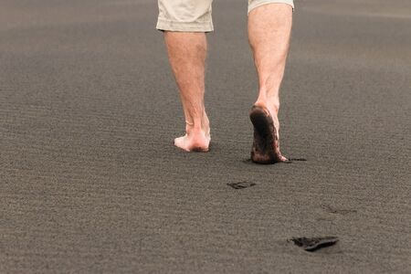 man walking barefoot on volcanic sand Stock Photo