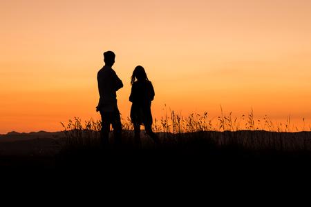 mujer mirando el horizonte: joven pareja admirando la puesta de sol