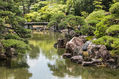 ponte giapponese: fiume che scorre attraverso giardino zen giapponese Archivio Fotografico