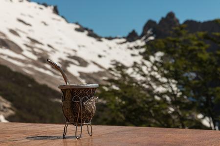 yerba mate: yerba mate de calabaza y bombilla con las montañas en el fondo