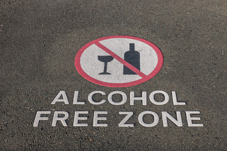 antisocial: closeup of alcohol free zone sign on pavement