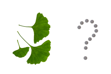 ginkgo biloba leaves with pills question mark on white background