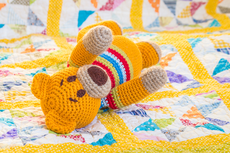 closeup of crochet teddy bear lying on quilt cover Imagens - 106066500