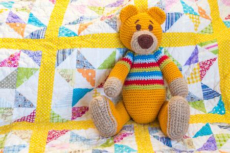 orangefarbener Teddybär, der auf buntem gestepptem Bettbezug sitzt